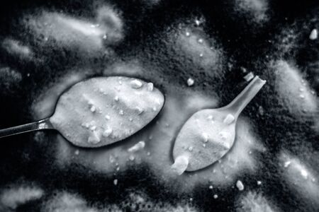 Raw powdered baking soda in a antique spoon on wooden surface along with some more in a plastic spoon. Horizontal and top shot. Imagens
