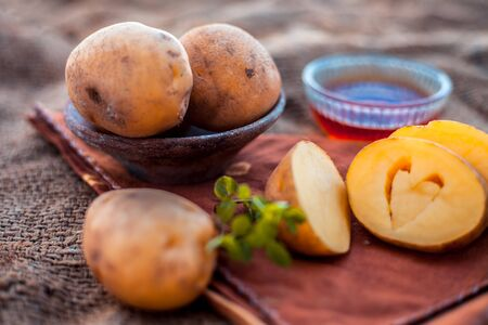 Potato juices face pack or face mask in a glass bowl on jute bags surface consisting of potato juice and honey.Used for skin whitening purpose along with entire ingredients.Horizontal low angle.