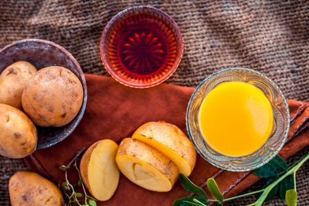 Potato juice's face pack or face mask in a glass bowl on jute bag's surface consisting of potato juice and honey.Used for skin whitening purpose along with entire ingredients.Horizontal top shot. Imagens - 128207504