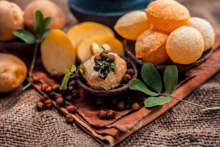 Famous Indian & Asian street food dish i.e. Golgappa snack in a clay bowl along with its flavored spicy water in another clay vessel. Horizontal shot of the snack and its ingredients present. Imagens - 128207648