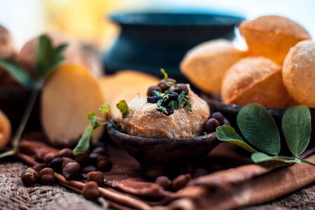 Famous Indian & Asian street food dish i.e. Golgappa snack in a clay bowl along with its flavored spicy water in another clay vessel. Horizontal shot of the snack and its ingredients present. Imagens - 128207649