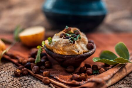 Famous Indian & Asian street food dish i.e. Golgappa snack in a clay bowl along with its flavored spicy water in another clay vessel. Horizontal shot of the snack and its ingredients present.