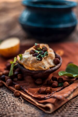 Famous Indian & Asian street food dish i.e. Golgappa snack in a clay bowl along with its flavored spicy water in another clay vessel. Vertical shot of the snack and its ingredients present. Фото со стока