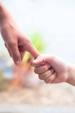 Hand of female child holding the hand of matured man, Shot with blurred background. Concept of Father's day. Men helping the female hand to overcome conquer obstacles and fears. Vertical shot. Banque d'images