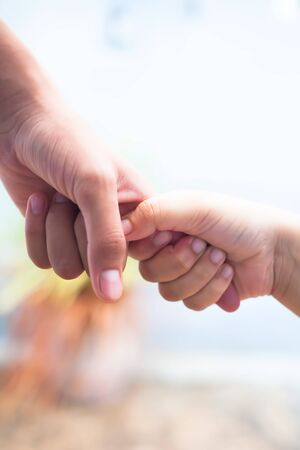 Hand of female child holding the hand of matured man, Shot with blurred background. Concept of Father's day. Men helping the female hand to overcome conquer obstacles and fears. Vertical shot. Stock Photo