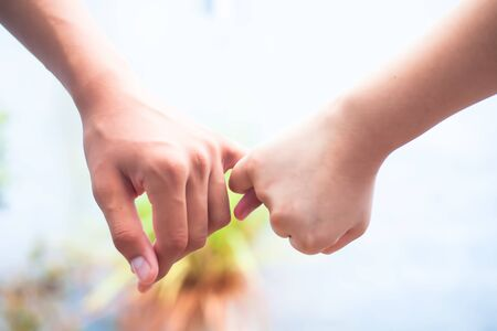Female child's hand holding the hand of elder male shot with bokeh background and horizontal. Concept of father's day ( 16th June). Banco de Imagens