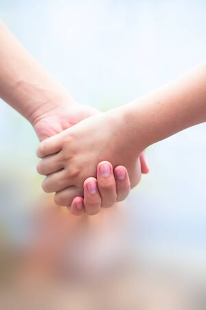 Hand of female child holding the hand of matured man, Shot with blurred background. Concept of Father's day. Men helping the female hand to overcome conquer obstacles and fears. Vertical shot. Banco de Imagens