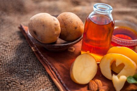 Glowing face mask of potato juice in a glass bowl on brown colored surface along with some Potato juice,honey and almond oil.Horizontal shot.To eliminate skin rashes, remove impurities,etc. Imagens