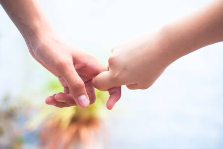 Female child's hand holding the hand of elder male shot with bokeh background and horizontal. Concept of father's day ( 16th June).