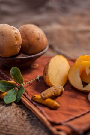 Potato face mask consisting of grated potato and some turmeric powder or haldi in a glass bowl on jute bags surface to brighten the skin, kills bacteria and germs.