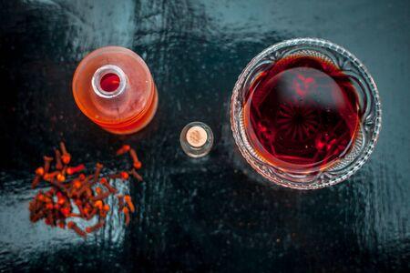 Maschera per il viso ai chiodi di garofano per la prevenzione contro l'acne e i brufoli su una superficie di legno in una ciotola di vetro insieme a olio di chiodi di garofano e un po' di olio di cocco.