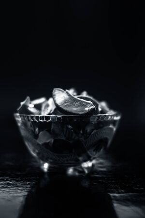 Raw cut aloevera or aloe vera gel in a glass bowl on wooden surface along with its reflection on the surface.