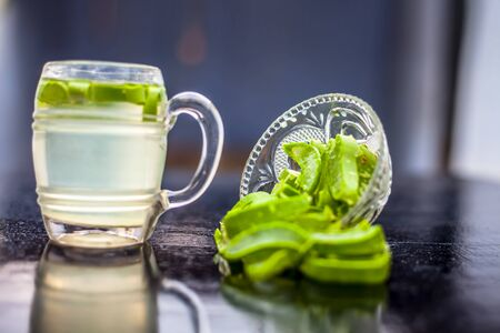 Close up of glass mug on wooden surface containing aloe vera detox drink in along with its entire raw ingredients with it.