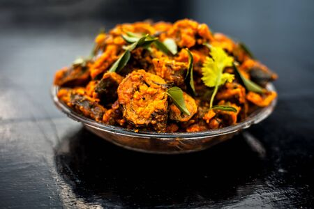 Famous Indian & Gujarati snack dish in a glass plate on wooden surface i.e. Patra or paatra consisting of mainly Colocasia esculenta or arbi ke pan or elephant ear leaves and spices. Stok Fotoğraf