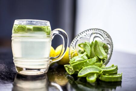 Close up of glass mug on wooden surface containing aloe vera and lemon juice detox drink along with its entire raw ingredients with it. Horizontal shot with blurred background.