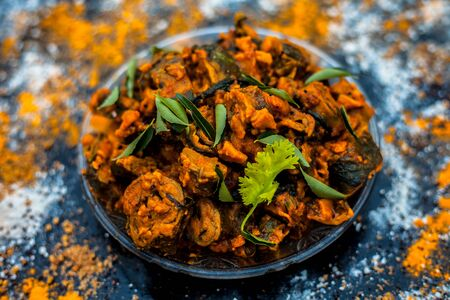 Famous Indian & Gujarati snack dish in a glass plate on wooden surface i.e. Patra or paatra consisting of mainly Colocasia esculenta or arbi ke pan or elephant ear leaves and spices. Horizontal shot.