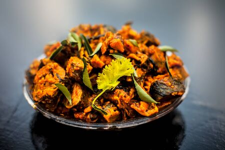 Famous Indian & Gujarati snack dish in a glass plate on wooden surface i.e. Patra or paatra consisting of mainly Colocasia esculenta or arbi ke pan or elephant ear leaves and spices. Stok Fotoğraf - 131634380