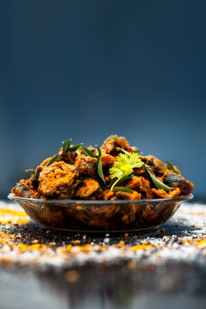 Famous Indian & Gujarati snack dish in a glass plate on wooden surface i.e. Patra or paatra consisting of mainly Colocasia esculenta or arbi ke pan or elephant ear leaves and spices. Vertical shot.