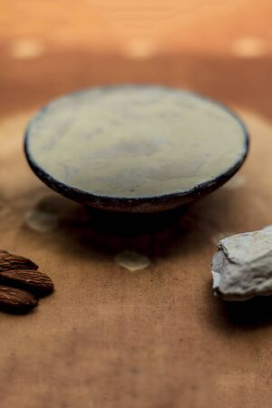 Fuller's earth face mask in a clay bowl on brown fabric's surface along with some milk and almonds. For softer skin.