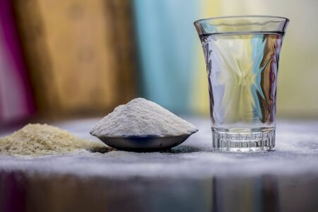 Rice water in a glass bowl along with rice grains & its powder also on wooden surface & some rice power spread on the surface for the treatment of various things such as Home Remedy,Beauty & Health.