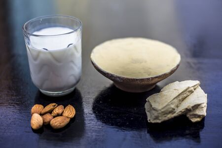 Face mask of multani mitti or mulpani mitti or fuller's earth in a clay bowl on the wooden surface well mixed with milk and almonds. For the treatment of softer skin.
