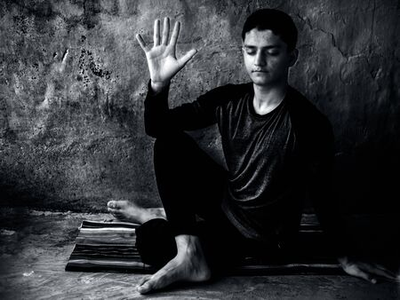 Half Lord of the Fishes Pose or Ardha Matsyendrasana performed by a caucasian young man on the colorful mat by wearing black attire.