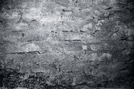 Close up of a shot of texture or background of a brick wall or adobe wall with some green and dried algae on it.