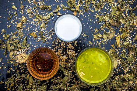 Neem or Indian Lilac face mask on the black wooden surface for Anti-aging benefits of neem leaves paste, oatmeal, milk, and honey.
