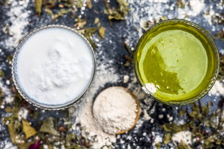 Neem or Indian Lilac face mask on the black wooden surface for acne and scars consisting of gram flour, neem paste, and some curd.