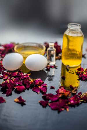Trio pack of herbs and ingredients to fight dandruff on the wooden surface well mixed in a glass bowl which are castor oil, coconut oil, and egg. Also used to treat itchiness and to deep condition.