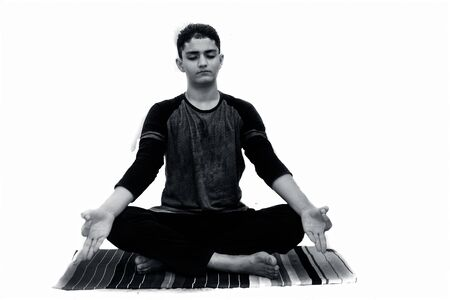 Portrait shot of the young man doing Lotus position or Padmasana or cross-legged sitting asana on a colorful mat with wearing black attire isolated on white background.