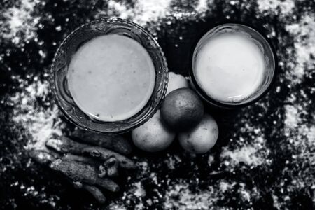 Lemon face mask on the wooden surface consisting lemon juice, gram flour or chickpea flour, turmeric or Haldi and milk in a glass bowl.For the treatment of tans.