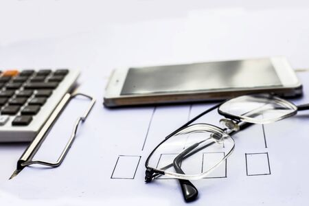 Close up of workplace of businessman or finance consultant isolated on white using credit card, cell phone, pen and calculator like things and some coins also.