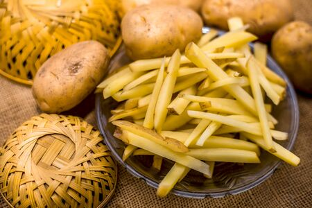 Raw cut french fries in a transparent glass plate along with raw potato with it on jute bags surface.