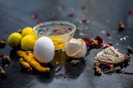 Face mask of lemon juice, honey, and curd along with some raw turmeric well mixed in a glass bowl along with entire raw ingredients on the wooden surface for acne-prone skin and blemishes. Imagens