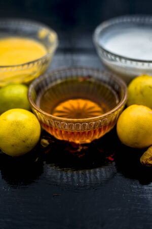 Face mask of lemon juice, honey, and curd along with some raw turmeric well mixed in a glass bowl along with entire raw ingredients on the wooden surface for acne-prone skin and blemishes. Stock Photo
