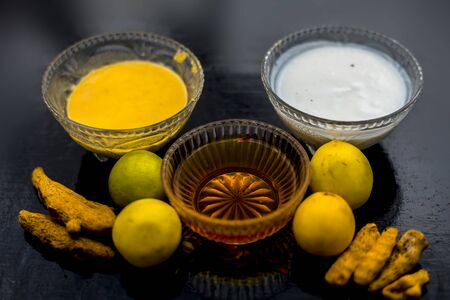 Face mask of lemon juice, honey, and curd along with some raw turmeric well mixed in a glass bowl along with entire raw ingredients on the wooden surface for acne-prone skin and blemishes. 免版税图像