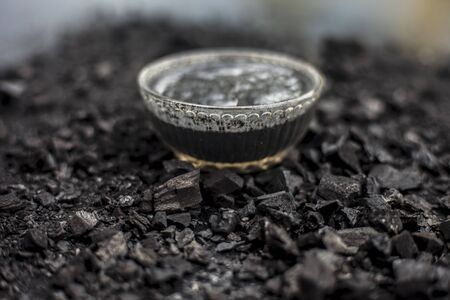 Close up of activated charcoal in a glass bowl on the wooden surface along with some raw powder of charcoal or coal spread on the surface. Stock Photo