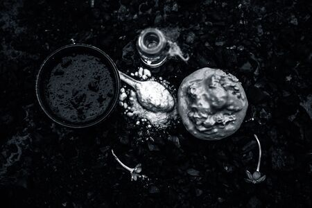 Activated charcoal face mask consisting of bentonite clay or fuller's earth or multani mitti or mulpani mitti well mixed with baking soda and coconut oil. On a wooden surface with entire constituents.