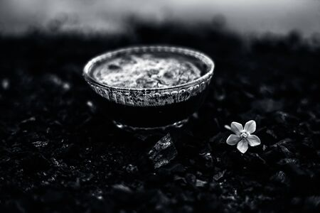 Close up of activated charcoal in a glass bowl on the wooden surface along with some raw powder of charcoal or coal spread on the surface.
