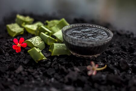 Aloe vera gel hair mask in a glass bowl consisting of activated charcoal & some aloe vera gel. To detoxify and deodorize your hair, On the wooden surface in dark colors.