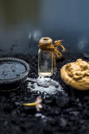 Activated charcoal face mask consisting of bentonite clay or fullers earth or multani mitti or mulpani mitti well mixed with baking soda and coconut oil. On a wooden surface with entire constituents. Stock Photo