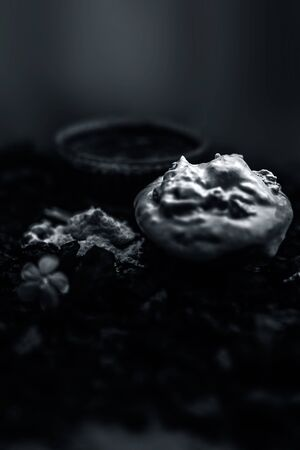 Activated charcoal face mask consisting of bentonite clay or fullers earth or multani mitti or mulpani mitti well mixed with baking soda and coconut oil. On a wooden surface with entire constituents. Фото со стока