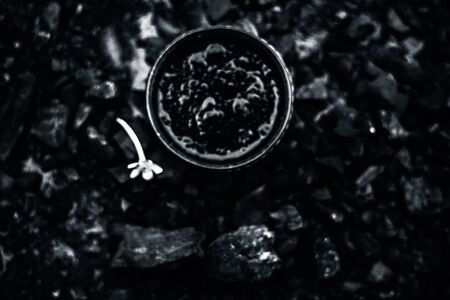 Close up of activated charcoal in a glass bowl on the wooden surface along with some raw powder of charcoal or coal spread on the surface. Фото со стока