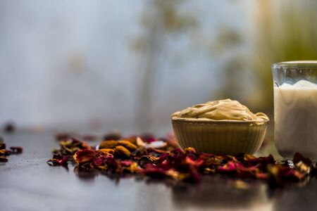 Multani mitti or fullers earth or mulpani mitti face mask on wooden surface in glass bowl consisting of milk, almonds, and bentonite clay.For the treatment of softer skin.