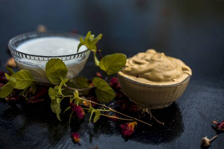 Homemade DIY face mask on the wooden surface consisting of yogurt,multani mitti or mulpani mitti (fullers earth) and mint leaves in a glass bowl. For the treatment removal of dark patches.