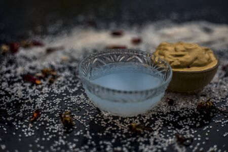 Ubtanface maskface pack of Multani mitti or fullers earth on wooden surface in a glass bowl consisting of Multani mitti and coconut oil for the remedy or treatment of suntan.On the wooden surface.