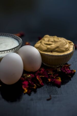 Best DIY face mask of multani mitti or mulpani mitti along with egg white and some yogurt well mixed in a glass bowl on the black wooden surface for the remedy of even skin. Banco de Imagens
