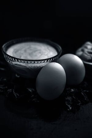 Best DIY face mask of multani mitti or mulpani mitti along with egg white and some yogurt well mixed in a glass bowl on the black wooden surface for the remedy of even skin. 写真素材