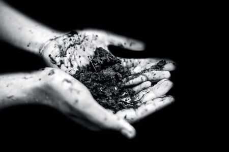 Close up of hands of a farmer holding new fresh soil after rain in his hands and showing to the camera.